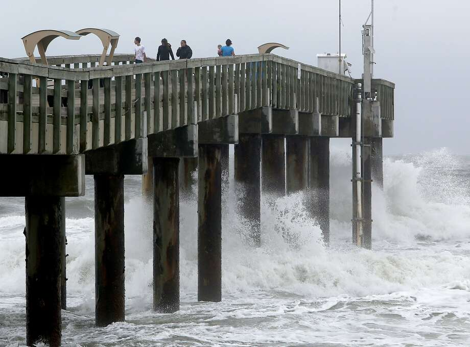 People stand on the pier as waves crash below as Hurricane Matthew approaches St. Augustine, Fla., about 90 minutes from Gainesville. Photo: Matt Stamey, Associated Press