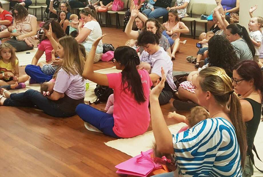 Mothers raise their hands during the Global Big Latch On at Kingwood Medical Center to indicate their participation in a worldwide simultaneous breastfeeding initiative Saturday, Aug. 6.