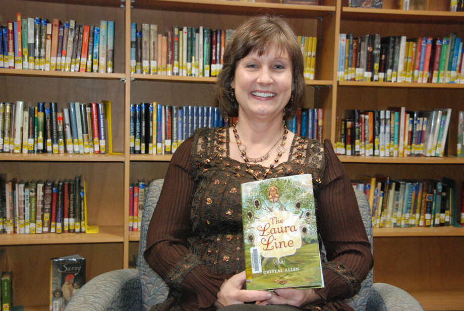 """Dean Middle School librarian Sandra Pallante displays author Crystal Allen's book, """"The Laura Line."""" Allen is one of six authors who will appear at the Cy-Fair Book Festival onMarch 8."""