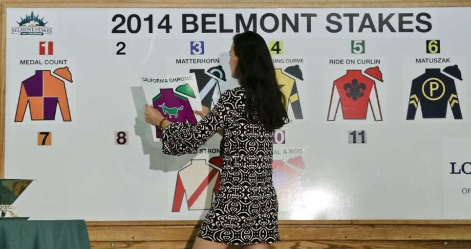 A New York Racing Association aide hangs California Chrome's name in the number two post position during the draw for the Belmont Stakes on Wednesday in Elmont, N.Y.