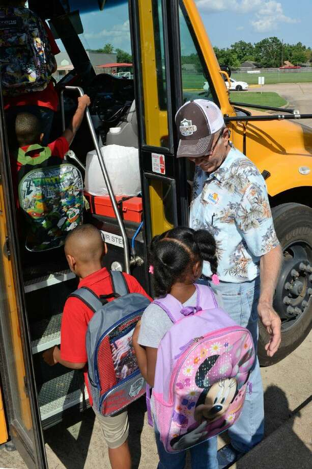 Bus Buddy Paul Morgan greets Francone Elementary School students as they enter the bus on the first day of school on Aug. 24, 2015. Registration for the 10th annual Bus Buddies program kicks off on Aug. 10.