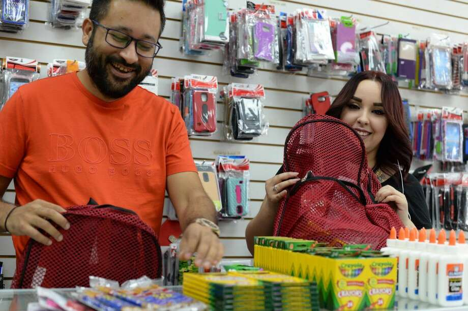 Sunny Mohammed and an employee, Jackie Hernandez, preparing backpacks to give to area children. Mohammed is hosting his second annual Backpack Giveaway this Wednessday at 4 p.m. at 137 W. Southmore in front of AB Wireless.