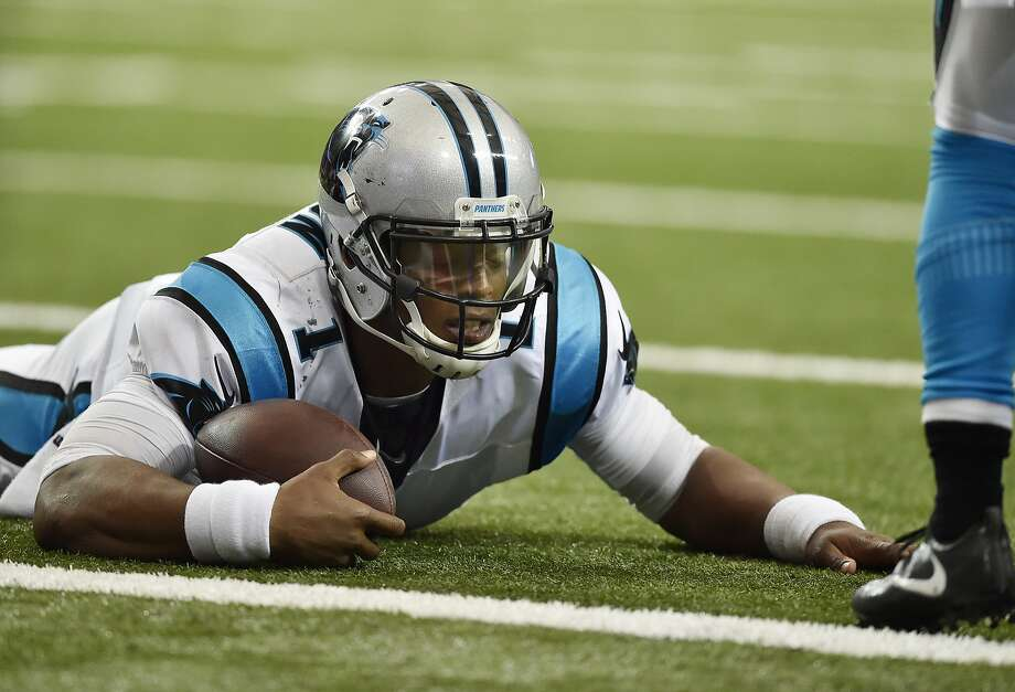 Panthers quarterback Cam Newton lies on the turf after being hit against the Falcons on Sunday. Photo: Rainier Ehrhardt, Associated Press