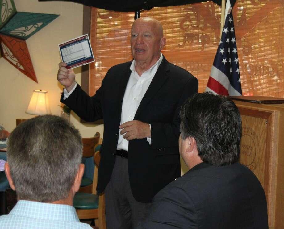 "U.S. Rep. Kevin Brady presents a copy of a simple, fair, ""postcard"" tax filing system. Photo: Jacob McAdams"