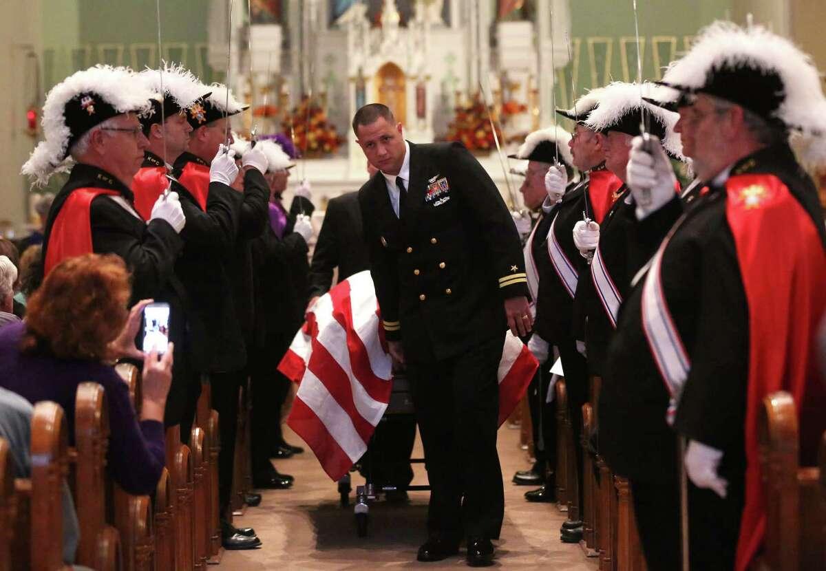 Lt. Brian Lewis escorts the casket before the Mass of remembrance for Chaplain Aloysius Schmitt on Wednesday at St. Luke's Church in St. Lucas, Iowa. Schmitt, a St. Lucas, native, died Dec. 7, 1941.