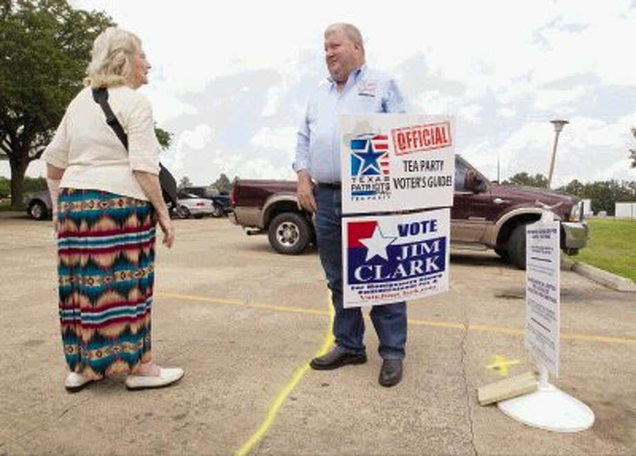 Montgomery County Precinct 4 commissioner candidate Jim Clark talks with Election Judge Martha Williams at the East Montgomery County Annex building in New Caney Thursday. Election officials painted a yellow line around the courthouse after a conflict between political opponents. Photo: Jason Fochtman / Conroe Courier / HCN