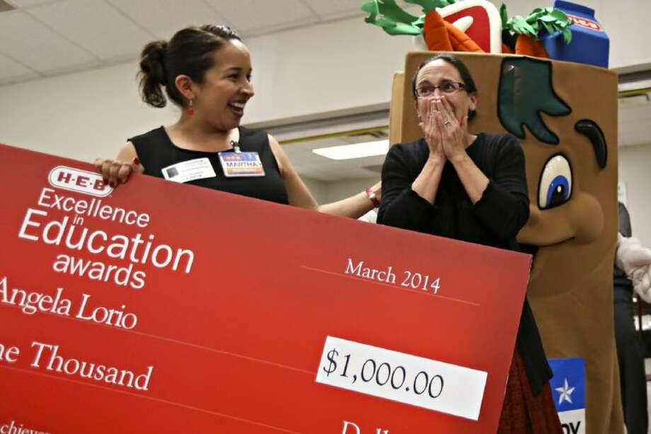 Angela Lorio, an ALPHA Academy teacher, right, reacts as Martha Barrera, Public Affairs H-E-B Houston, left, announces Lorio as a finalist for the 2014 H-E-B Excellence in Education Award and presents her a $1,000 check on Wednesday, April 2, at the ALPHA Academy in Magnolia. Photo: Michael Minasi