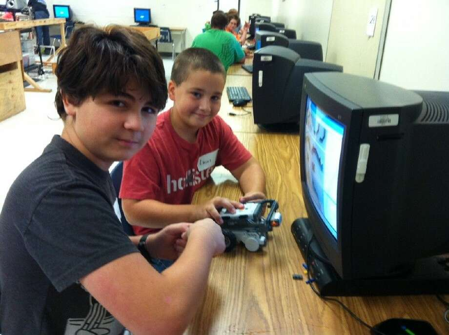 """Cole and Lucas, sixth-grade Dayton ISD students, add an engine to their robot, """"Power-saw."""" Photo: STACEY GATLIN"""