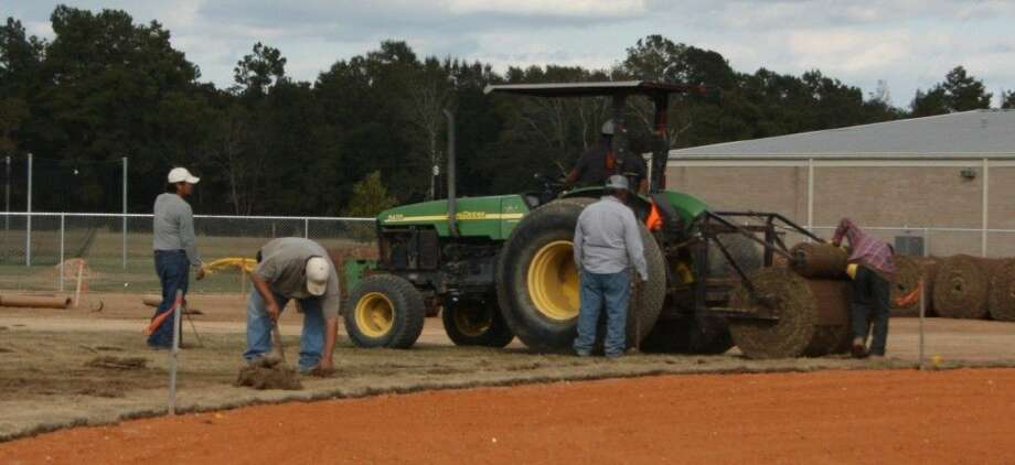 Workers diligently tend to the baseball field at Tarkington ISD on Nov. 20. The renovation work on the field is expected to be finished in time for baseball season. Photo: Jacob McAdams