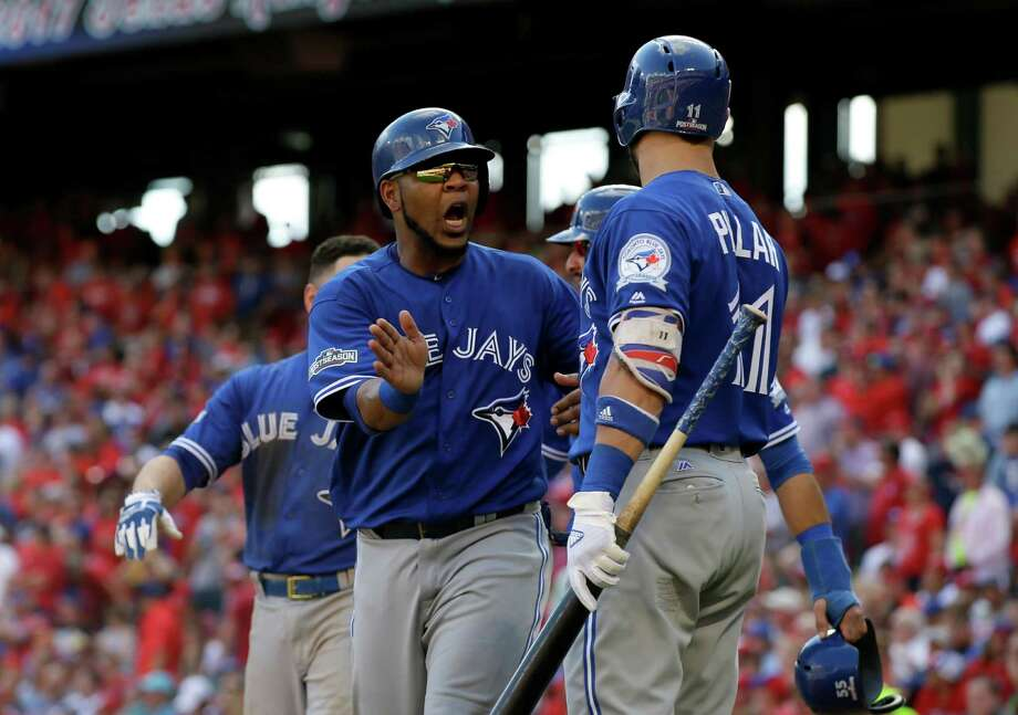 Toronto Blue Jays' Edwin Encarnacion celebrates with Kevin Pillar (11) after scoring on a bases-clearing triple by Troy Tulowitzki in the third inning of baseball Game 1 of the American League Division Series against the Texas Rangers on Thursday, Oct. 6, 2016, in Arlington, Texas. Photo: LM Otero, AP / Copyright 2016 The Associated Press. All rights reserved.