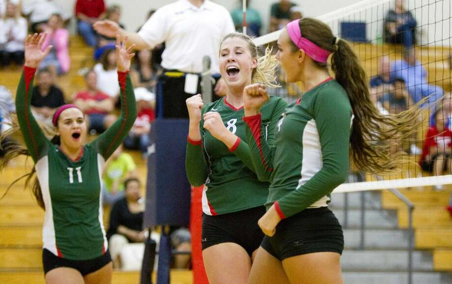 The Woodlands' Rachel Reed, center and Courtney Quinn, left, celebrates after a kill shot by Kendall Cook during a high school volleyball game at The Woodlands High School Tuesday. The Woodlands defeated Atascocita in straight sets. To view or purchase this photo and others like it, visit HCNpics.com. Photo: Jason Fochtman