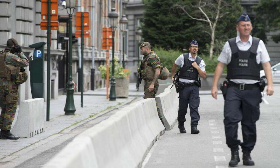 Police and soldiers from the Belgian Army secure an area in front of the Belgian Prime Minister's office, prior to a media conference in Brussels on Sunday. A man attacked two police officers with a machete near the police headquarters in Charleroi, Belgium on Saturday before being apprehended.