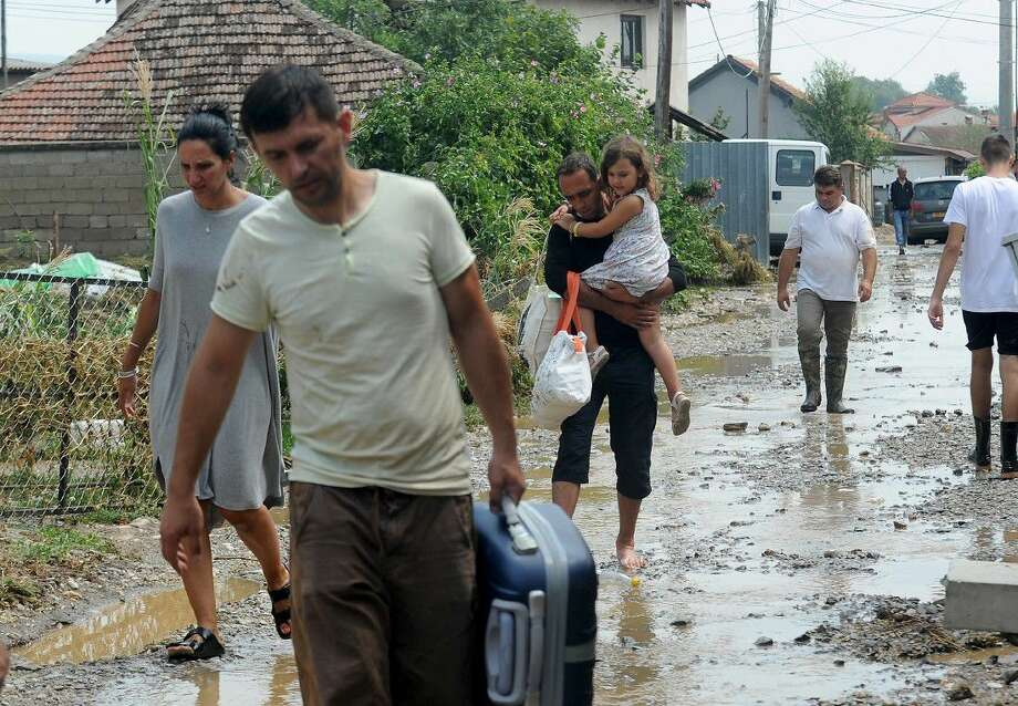 People carry their belongings fleeing from their flooded houses after an overnight storm at the village of Stajkovci, just east of Skopje, Macedonia, Sunday. The Macedonian capital of Skopje has been hit Saturday night by torrential rain and floods that left at least 17 people dead, six missing and sent 60 others to the hospital.