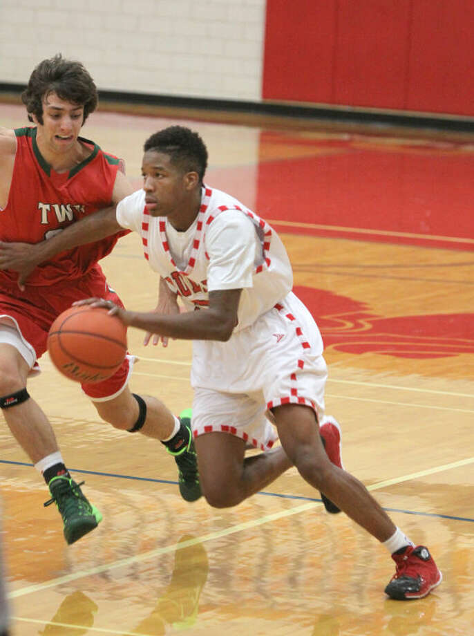 Dulles' Braylin Simmons drives on The Woodlands' Aaron Kovach during game in the Fort Bend Classic Basketball Tournament Dec. 12 at Dulles High School in Sugar Land. The Vikings have won nine consecutive games since the tournament. Visit HCNPics.com for more photos. Photo: Alan Warren/HCN