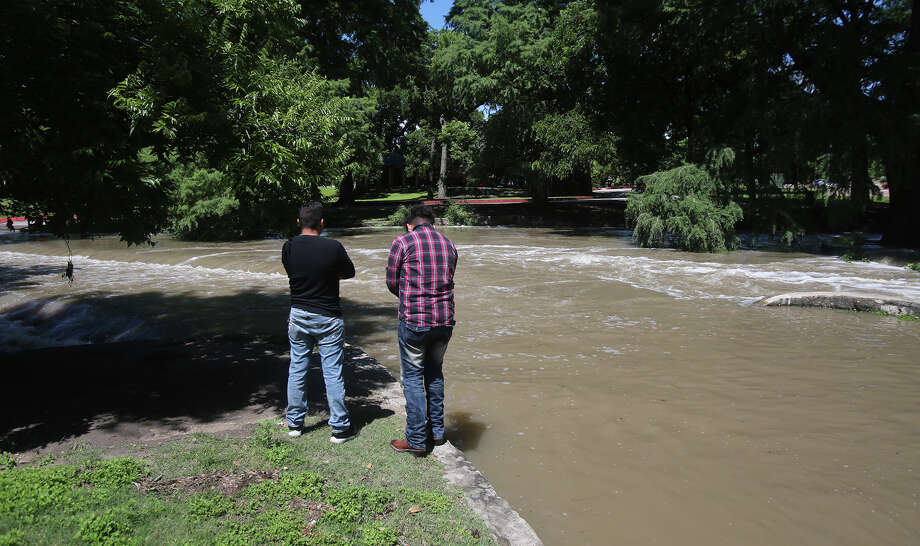 Christian Esquivel (left) and Germy Suarez check out the overflowing San Antonio River on June 2 at Brackenridge Park after heavy rain fell in the San Antonio area overnight. Photo: John Davenport /San Antonio Express-News / ©San Antonio Express-News/John Davenport