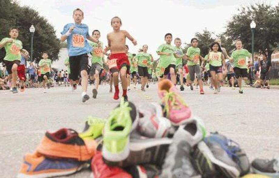 Children participate in the Barkley Shoe Dash near Heritage Place Park in downtown Conroe Saturday. Participants started the race with one shoe, ran 50 yards and put on the other shoe from a pile of competitors shoes, then dashed back to the finish line. To view or purchase this photo and others like it, visit HCNpics.com.