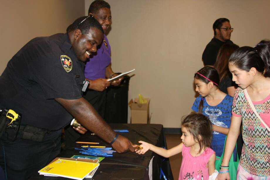 Cleveland Police Officer Jarrod Morton and Police Chief Darrel Broussard hand out spiral notebooks to children during the Second Annual Back-to-School Spectacular on Friday, Aug. 5, at the Cleveland Civic Center. Photo: Vanesa Brashier