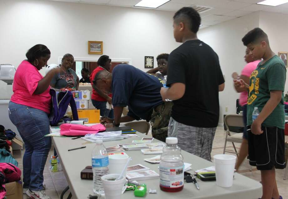 A member of Spring Hill Baptist Church (left) begins handing out backpacks to parents and children during the Back2School Extravaganza. Photo: Jacob McAdams