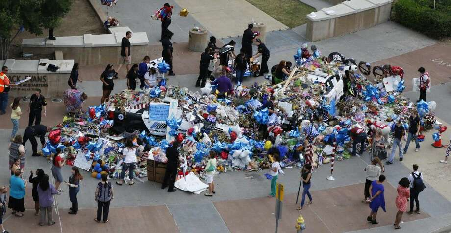 Dallas Police officers and volunteers help pick up notes, flowers, balloons and other items at a memorial at the Dallas police headquarters before a rain storm. Library archive experts have carefully sorted and saved items left outside the headquarters after last month's fatal shooting of five officers. Many objects will eventually be added to the Dallas History and Archive Collection.