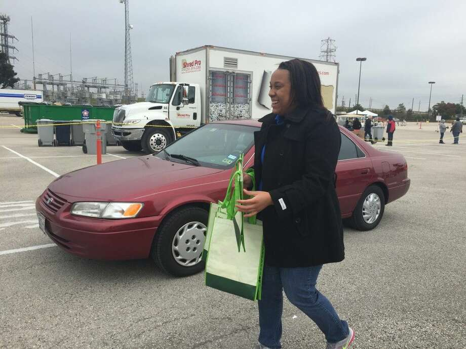 Volunteer Keisha Rhines passes out reusable goodie bags to people who dropped off materials at the recycling event Nov. 15. Each year the event recycles 40-50,000 pounds of materials.
