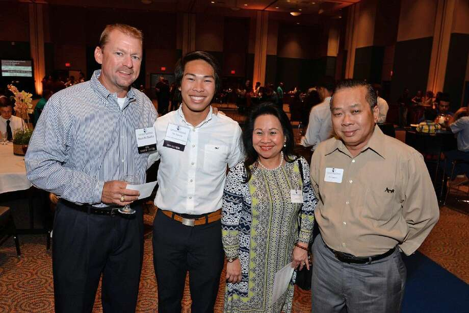 Mark McShaffry, Cy-Fair Educational Foundation board member, congratulates Cypress Falls High School graduate Viet Nguyen and his parents on his CFEF scholarship during the Aug. 2 scholarship reception at the Berry Center.