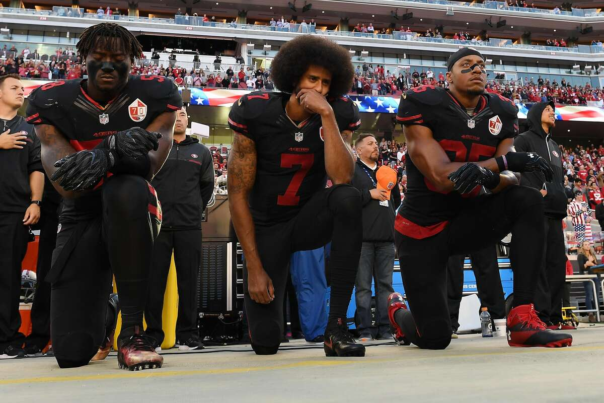 Eli Harold (left), Colin Kaepernick and Eric Reid of the San Francisco 49ers kneel in protest during the national anthem prior to their NFL game against the Arizona Cardinals at Levi's Stadium on October 6, 2016 in Santa Clara.