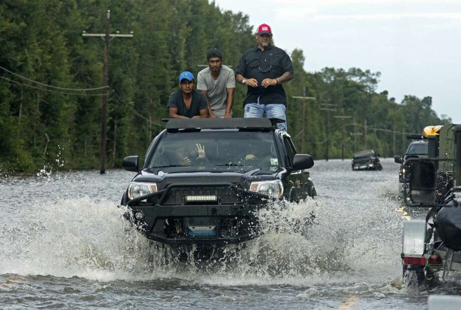 Motorists on Highway 190 drive through deep water through Holden, La., after heavy rains inundated the region, Sunday. Louisiana Gov. John Bel Edwards said Sunday that at least 7,000 people have been rescued so far.