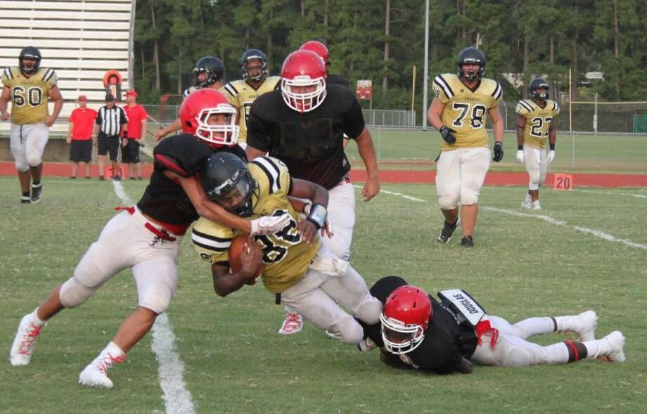 A trio of Cleveland Indians (black) tackle an Anahuac Panther, bringing him and the ball to the ground during their football scrimmage at Cleveland High School on Aug. 12. Photo: Jacob McAdams