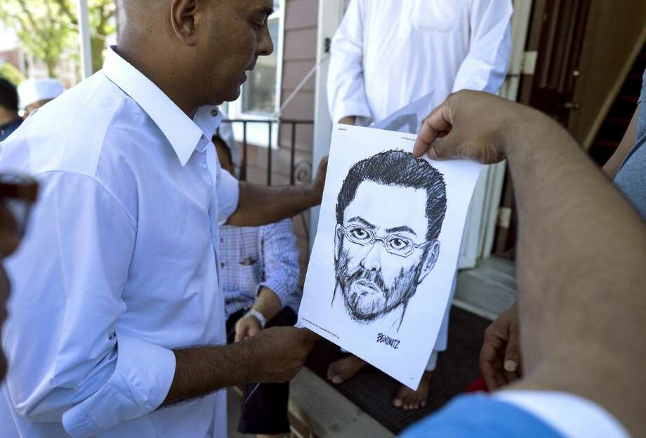 At the front entrance of the Al-Furqan Jame Masjid mosque in the Ozone Park section of Queens, a police sketch of a suspect believed to have shot the mosque's Imam is handed out by members of the mosque Sunday, a day after 55-year-old Imam Maulama Akonjee and his 64-year-old associate, Thara Uddin, were shot in the back of the head after they left the mosque following afternoon prayers Saturday.