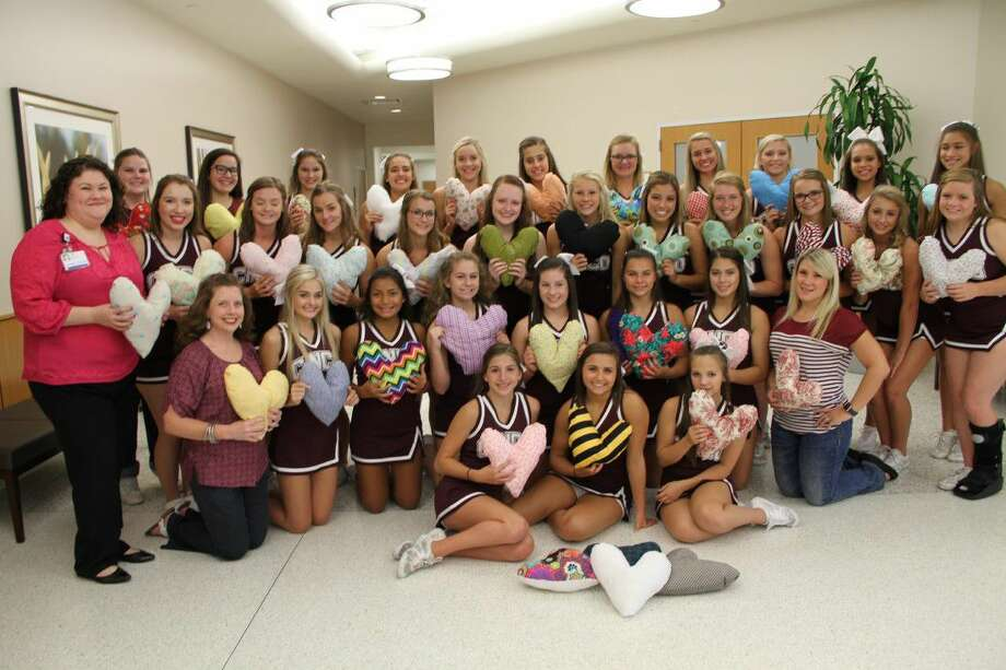 "Cinco Ranch High School cheerleaders present Houston Methodist Breast Care Center West with more than 200 handmade heart-shaped ""comfort pillows."" Photo: Submitted Photo"