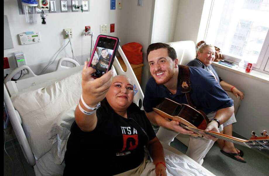 "Ponciano Seoane takes a selfie with Maria Martha Espinoza after he finished singing to her. The Methodist Hospital employee is competing on ""The Voice."" Photo: Ron Cortes / For The Express-News"