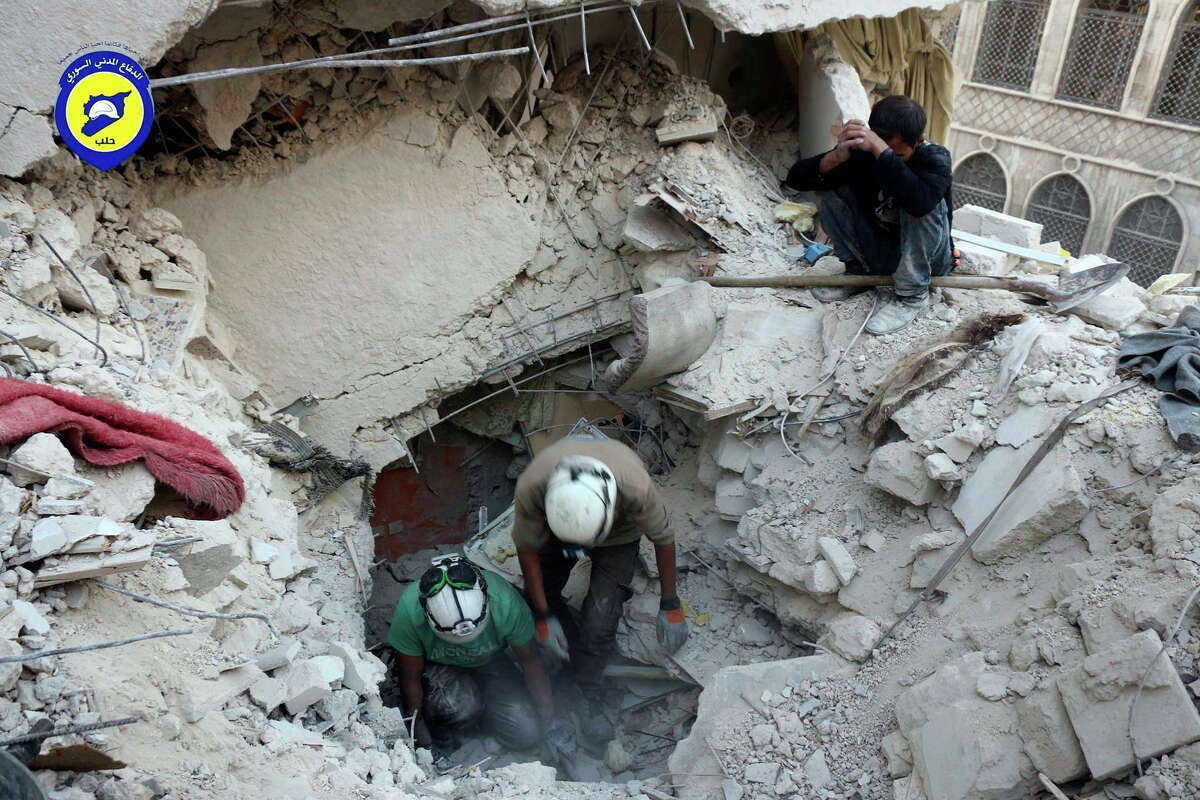 This Tuesday, Oct. 4, 2016 photo, provided by the Syrian Civil Defense group known as the White Helmets, shows Civil Defense workers from the White Helmets digging in the rubles to remove bodies and look for survivors, after airstrikes hit the Bustan al-Basha neighborhood in Aleppo, Syria. The U.N. on Wednesday released stark satellite images showing the most recent destruction of Syria's embattled northern city of Aleppo, pounded by Syrian and Russian airstrikes since the collapse of a U.S.-Russia brokered cease-fire two weeks ago. (Syrian Civil Defense White Helmets via AP) ORG XMIT: BEI102