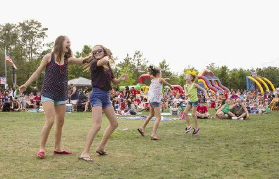 People dance as the Buck Yeager Band performs during a Memorial Day weekend celebration at Town Green Park in The Woodlands Sunday. Friends and families also enjoyed a firework show at the end of the night. Photo: Staff Photo By Ana Ramirez / The Conroe Courier