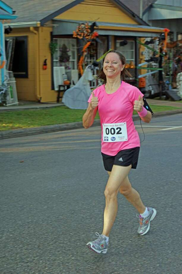 Tomball Police Department staffer Janet Barcelona completes the 5K run for breast cancer awareness through downtown Tomball in 2015. Photo: Submitted