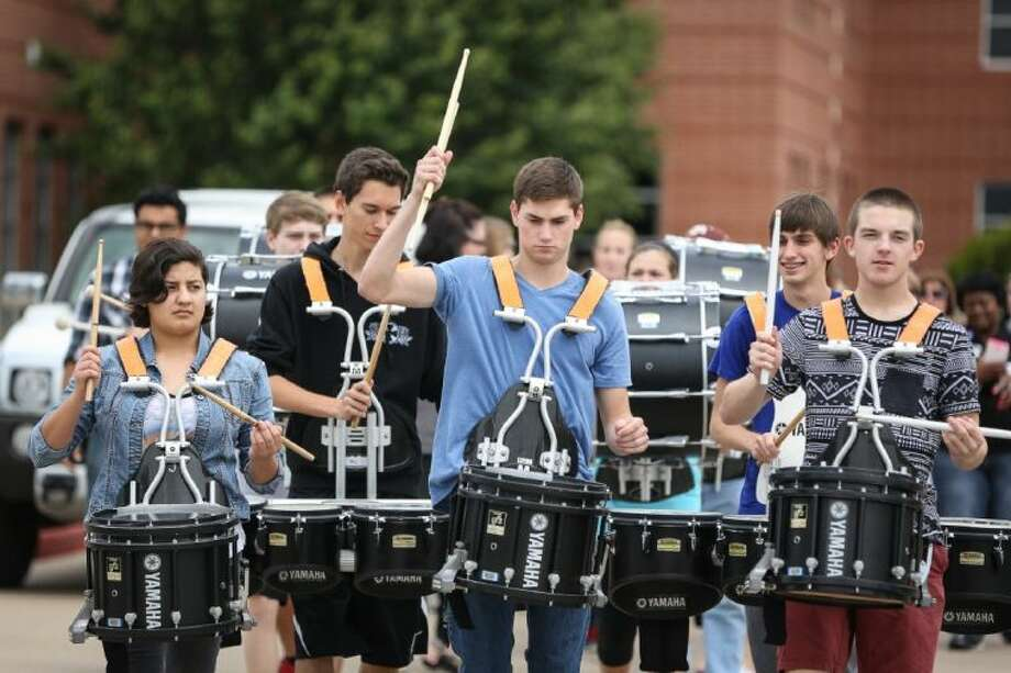 Cy Woods junior Blake Anglin and the rest of the school drumline lead a group of CFISD faculty and administrators from Cy Woods High School to Robison Elementary to take part in early voting on Thursday, May 1, 2014, in Cypress. Photo: Michael Minasi
