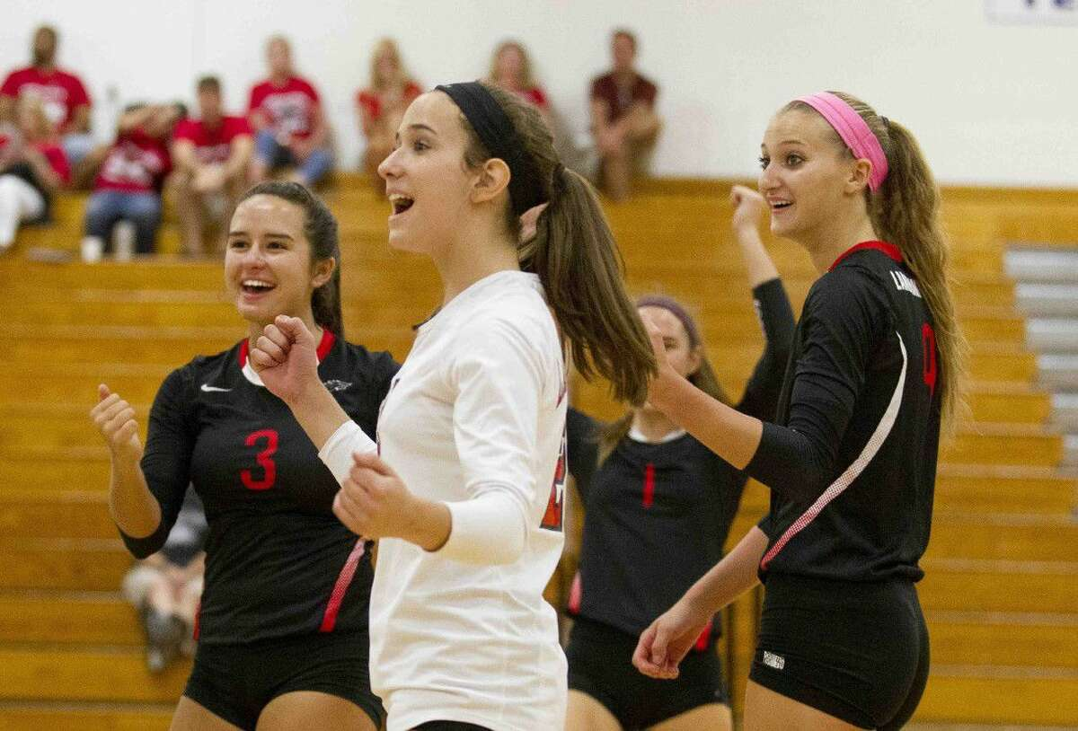 Langham Creek players celebrate a point in the second set of a volleyball match during the Katy/Cy-Fair Nike Invitational Saturday.
