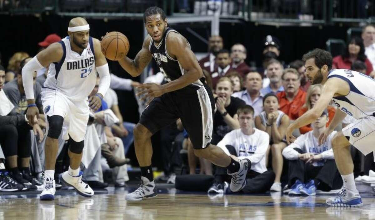 San Antonio Spurs forward Kawhi Leonard takes off past Dallas Mavericks guards Vince Carter, left, and Jose Calderon on April 10 in Dallas.