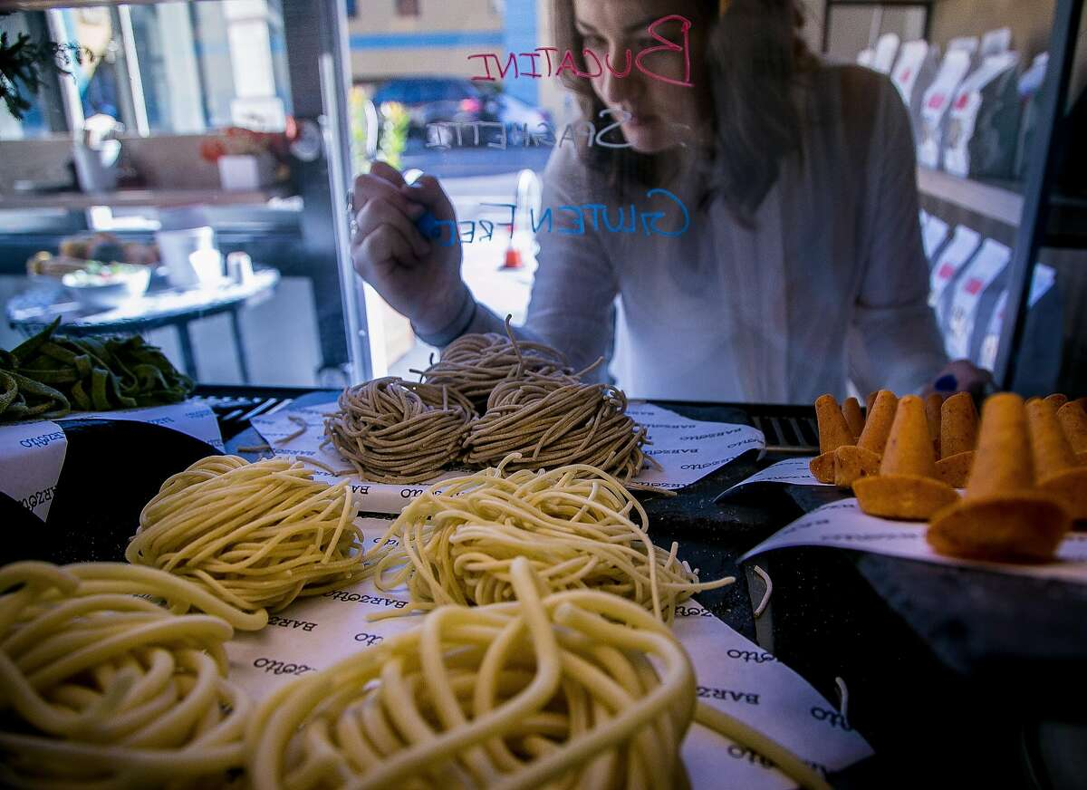 Julia Middlemiss writes the fresh pasta names on the case at Barzotto in San Francisco.