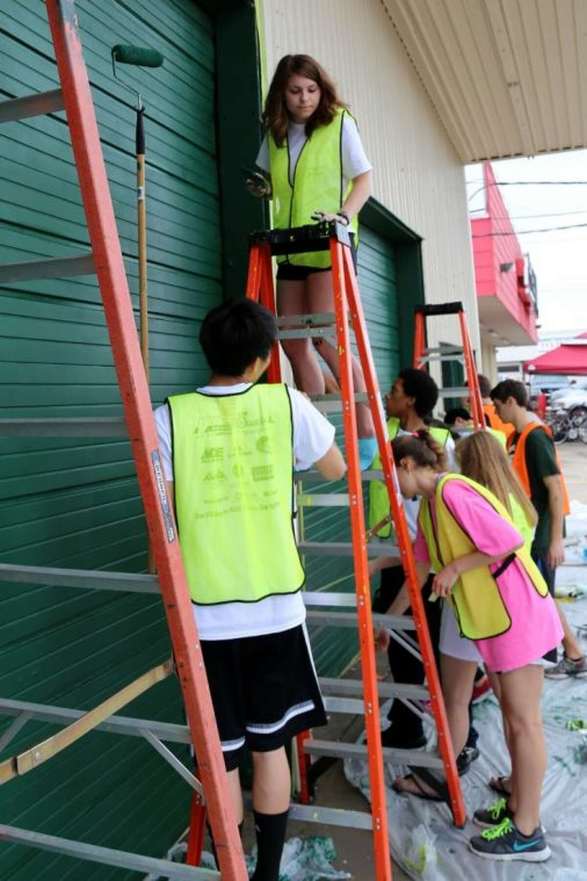 Stratford students put finishing touches Saturday on a garage door at Affordable Muffler.