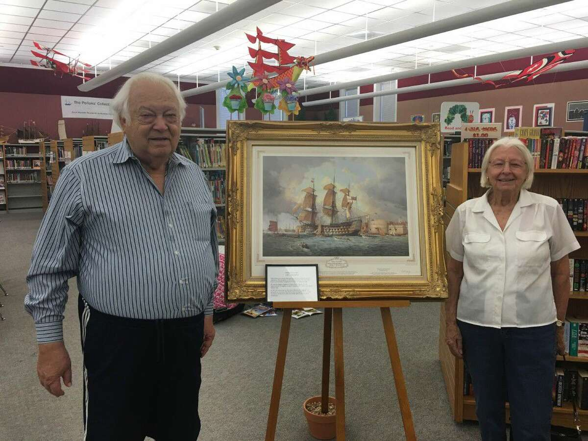 SubmittedAlex and Mary Pollak in front of one of their paintings they have collected through their travels at the front of Octavia Fields Branch Library in Humble.