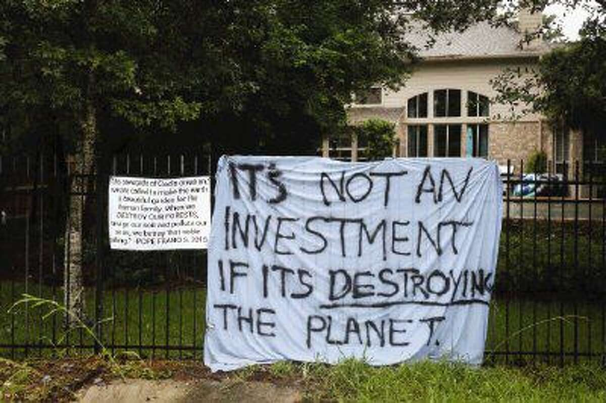 Residents living along Laurelhurst Circle are expressing dismay at tree clearing on the greenbelt separating the residents from St. Anthony of Padua Catholic Church by hanging banners along their backyard fences.