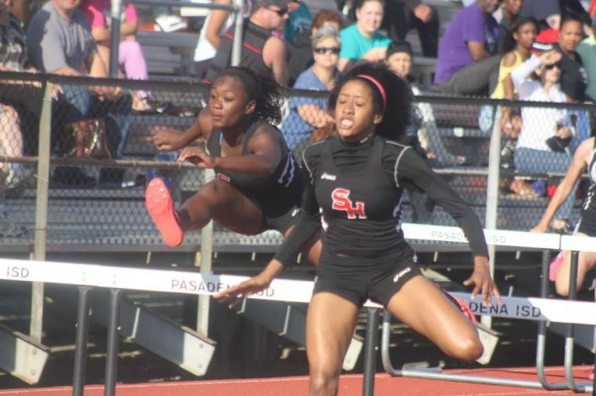 South Houston's Chelsie Decoud and teammate Keia Davis clear the final set of hurdles in the 100-meter event to capture first and second place during Thursday night's running finals to the 22-5A meet.