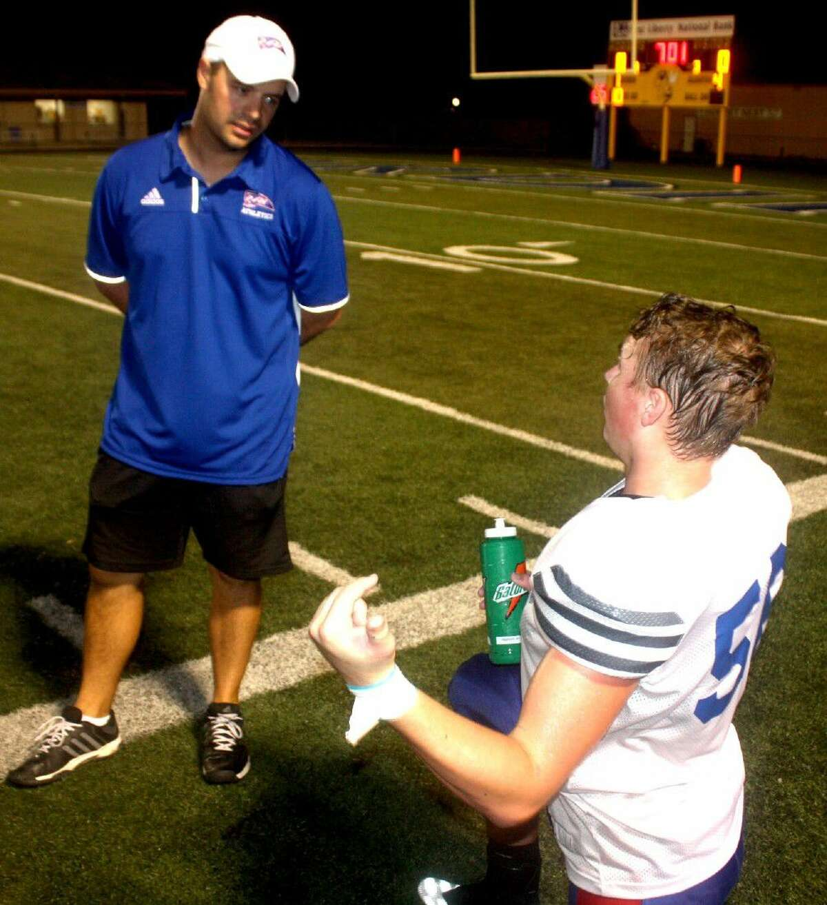 Walker Draeger attempts to explain something to head coach Justin Larsen during Thursday night's scrimmage against Hull-Daisetta.
