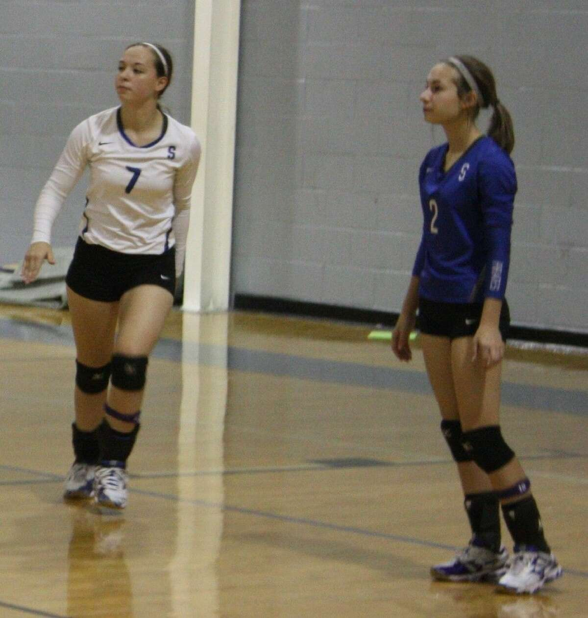 Shelby Brawner (7) of the Lady Pirates adjusts her position while Emily Brawner (2) watches the action from afar.