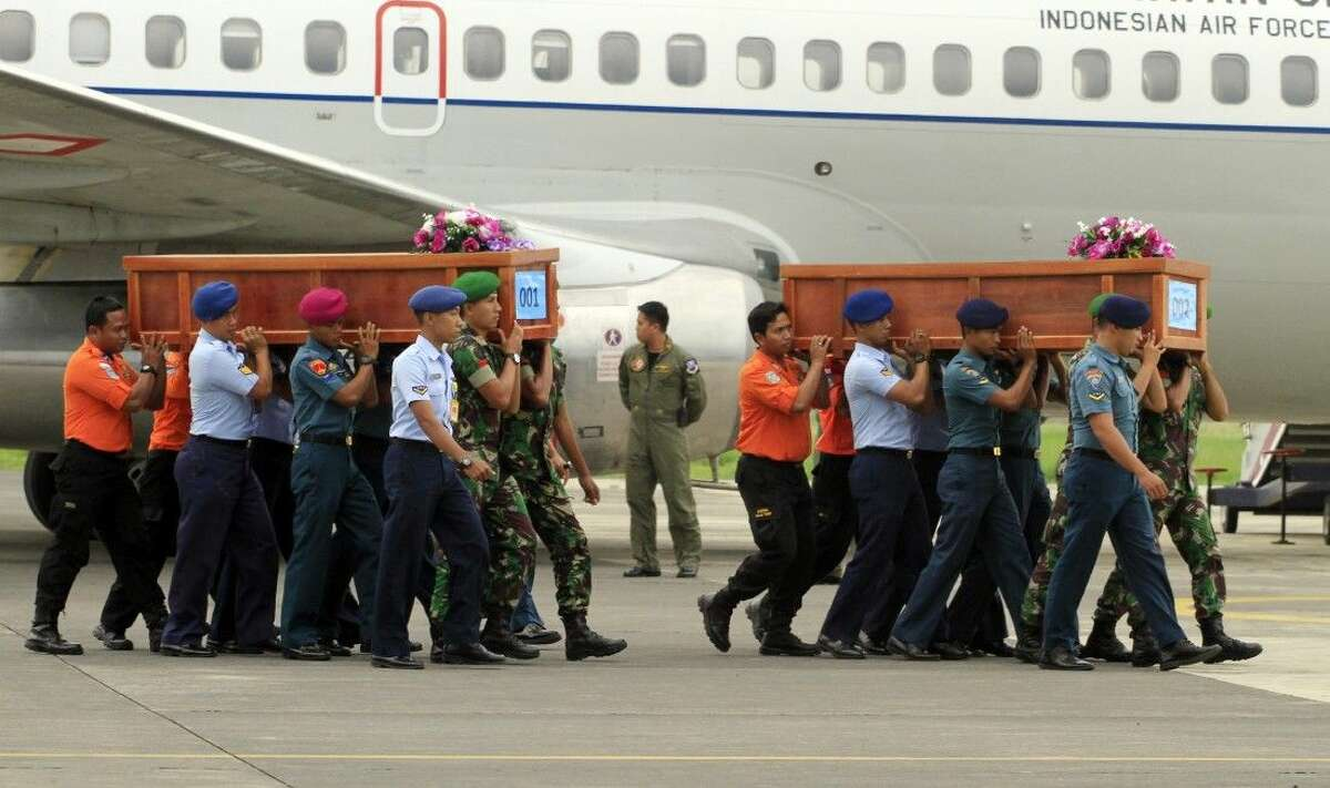Indonesian soldiers carry coffins containing bodies of victims of AirAsia Flight 8501 upon arrival Wednesday at Indonesian Military Air Force base in Surabaya.