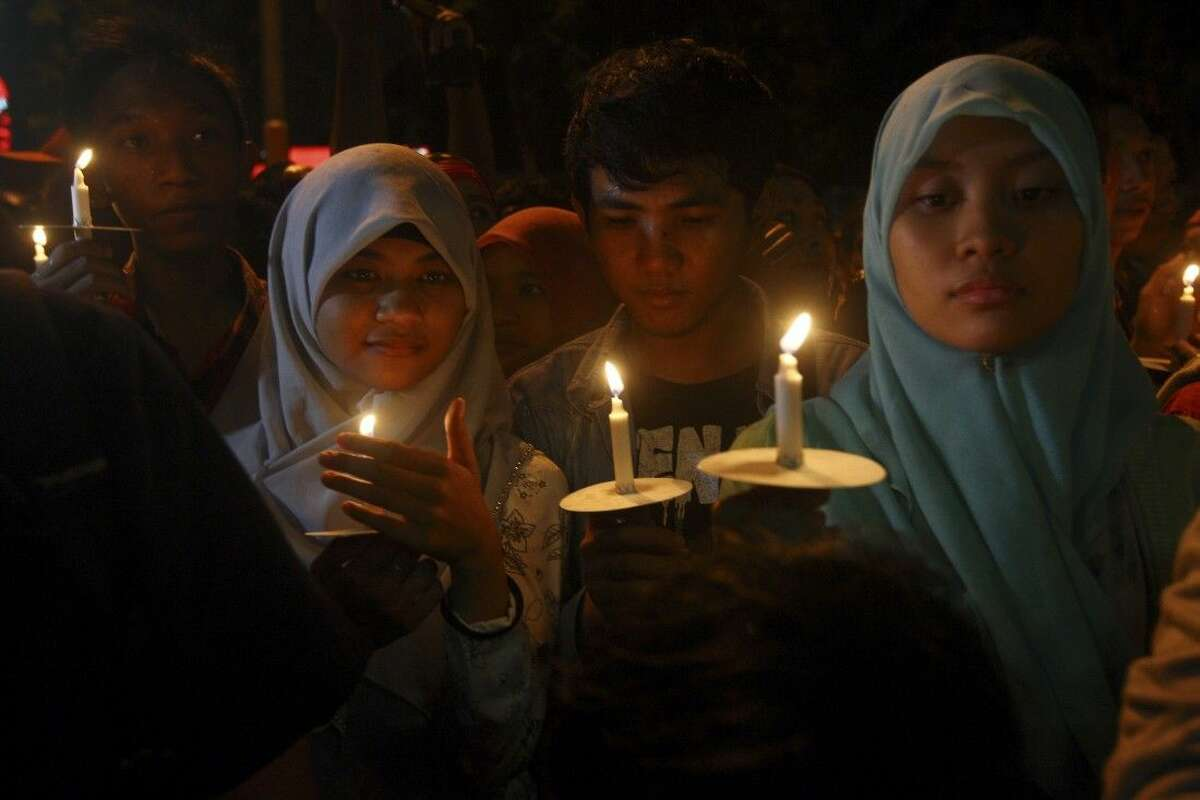 Indonesians hold candles Wednesday to pray for the victims of AirAsia Flight 8501.
