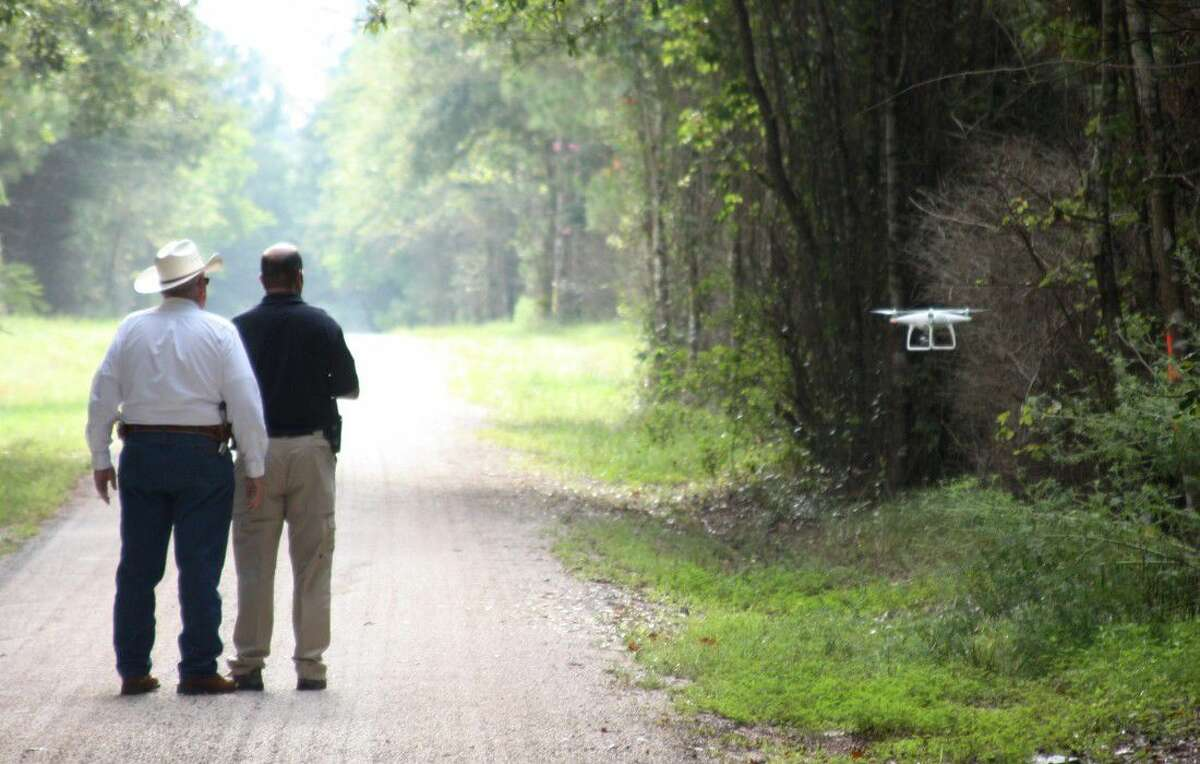 Liberty Police Lt. Chip Fairchild and Liberty County Sheriff's Investigator Don Neyland launch a drone helicopter to survey the area on Wells Cemetery Road in Cleveland where it is believed a local woman was killed on Monday, Aug. 15. Still images and videos taken by the drone will be used by the sheriff's office when they present their case to the district attorney's office and the grand jury. Eventually the photos could be used during the trial of the suspect accused of killing the woman.