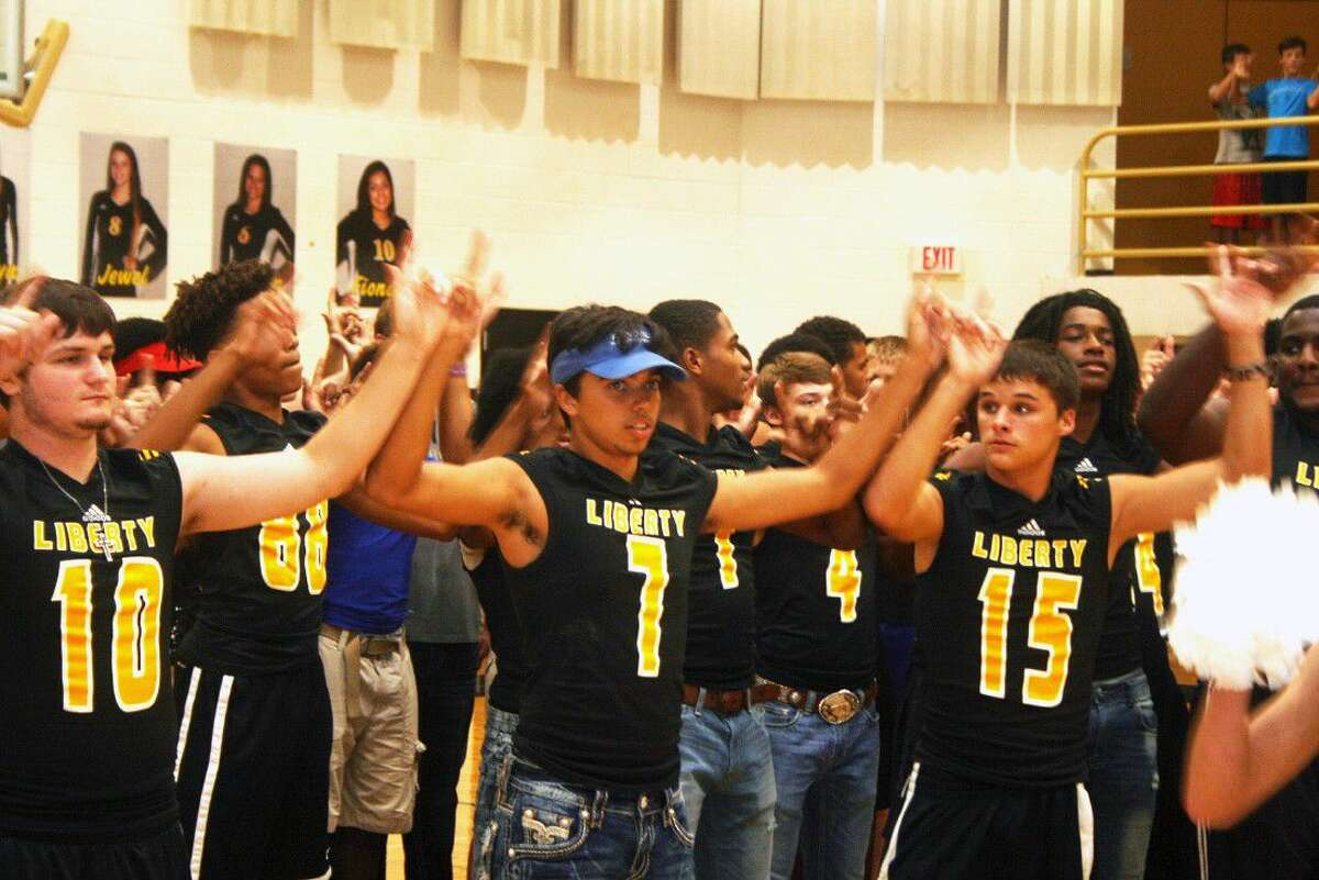 Members of the Panther football team have hands up as the band plays the school song at the Meet The Panther Night Thursday Aug. 18. Hundreds of fans packed the competition gym to cheer on their volleyball and football teams.