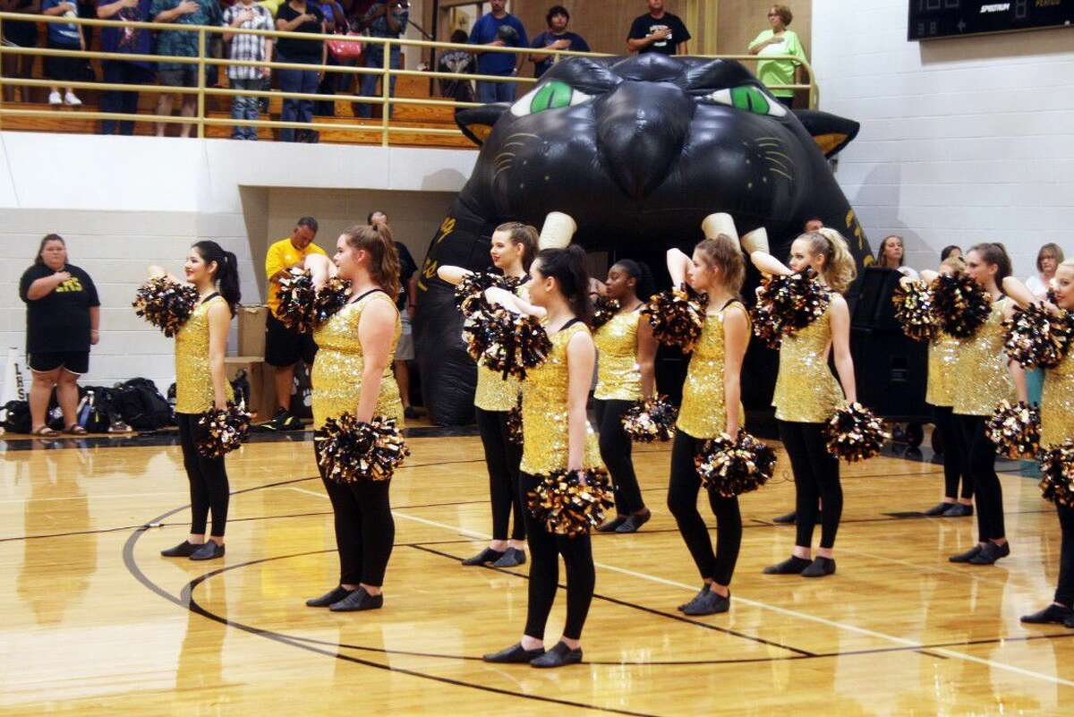 The Liberty High School Prancers drill team stand at attention during the singing of the national anthem.