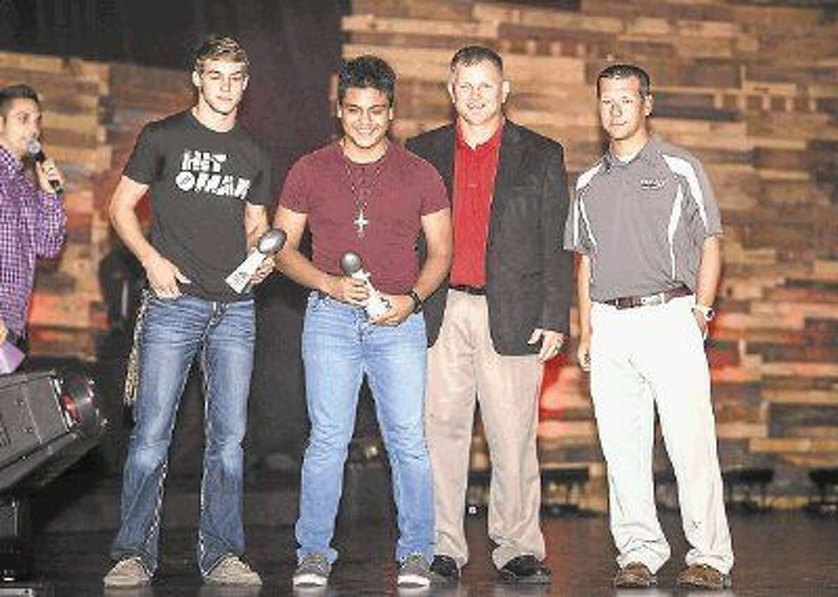 Caney Creek High School Hitman Award winner Zach Biles, left, pictured with Panthers assistant coach Leldon Hamilton; and Moorhead Junior High School Hitman Award winner Gabriel Garcia and coach Bo Picket.